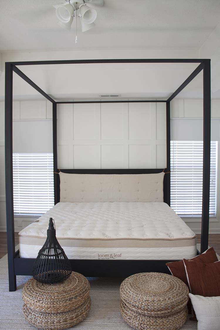 white room black canopy bed floor pillows